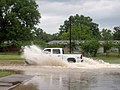 US Navy 100501-N-0000X-002 A vehicle navigates a street in the family housing section of Naval Support Activity Mid-South Saturday, May 1, 2010 during major flooding after heavy rains breeched nearby protective levees.jpg