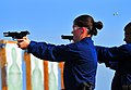 US Navy 100917-N-7948R-046 Operations Specialist 1st Class Jennifer Grieves fires a 9mm handgun during small arms training aboard the amphibious do.jpg