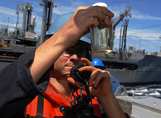 Jet fuel - A sailor inspects a sample of JP-5 jet fuel aboard an amphibious transport dock ship.