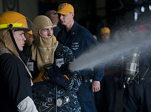 US Navy 120104-N-DX615-092 Boatswain's Mate 3rd Class Trevor Mink practices proper hose handling techniques during a general quarters drill aboard.jpg