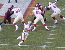 A quarterback rolls out to throw a pass while three linemen block their opponents at the line of scrimmage.