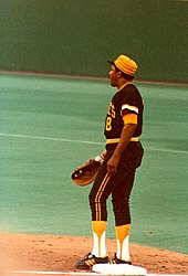 A man wearing a black and gold baseball uniform and baseball glove stands on first base.