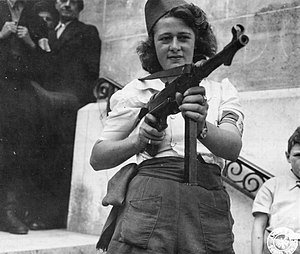 MP 40 - Simone Segouin, a French Partisan who captured 25 Germans in the Chartres area, in addition to executing others, poses with a German MP 40, with which she was most proficient.