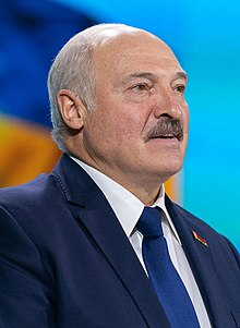 Lukashenko standing at a microphone, dressed in a suit