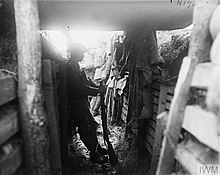 A member of the 1/7KR, stands in silhouette, while leaning on the wooden wall of a covered portion of a trench. Two additional soldiers stand in the background, in an uncovered part of the trench, almost washed out by the contrast.