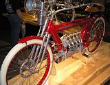 A bright red 1910 motorcycle with a flame headlamp, white rubber tires and a four-cylinder engine.