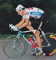A man on a bike in a cycling jersey.