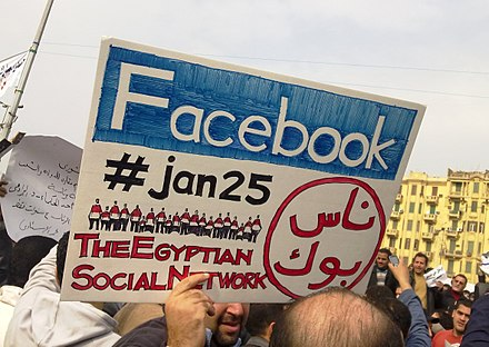 "A man during the 2011 Egyptian protests carrying a card saying ""Facebook,#jan25, The Egyptian Social Network"" 2011 Egyptian protests Facebook & jan25 card.jpg"