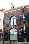 foto van Huis met gepleisterde lijstgevel. Twee voordeuren; de linkse met omlijsting. Op de verdieping vensters met kleine roedenverdeling