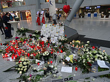 An airport interior with flowers piled against a pillar
