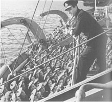 A man in a naval uniform addresses soldiers from a platform on a ship