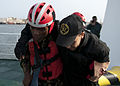 A Liberian coast guardsman, left, assists a Moroccan sailor portraying a casualty during maritime interdiction training aboard the Spanish Civil Guard patrol ship Rio Segura March 9, 2014, in Dakar, Senegal, as 140309-N-QY759-130.jpg