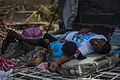 A Philippine resident and his daughter lay on a concrete slab in the aftermath of Typhoon Haiyan 131115-N-BD107-727.jpg