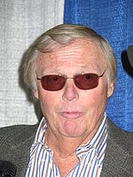 A man with light colored hair and sunglasses, looks straight forward, with a shocked look on his face.