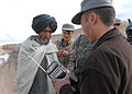 Afghan Police officer hands out radios keyed to RADIO GURESHK in Mayai Village, Gureshk district, Helmand Province,.jpg