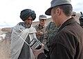 Afghan Police officer hands out radios keyed to RADIO GURESHK in Mayai Village, Gureshk district, Helmand Province,.jpg