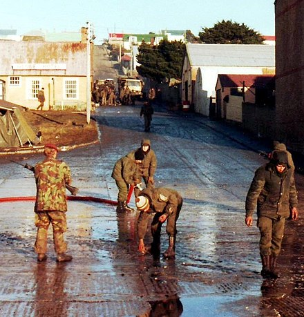 Argentinian troops being made to clear their trash from the streets of Port Stanley after their surrender in 1982 After war clean up Falklands 1982.jpg