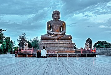 Large outdoor statue of Mahavira, with a seated worshipper for scale