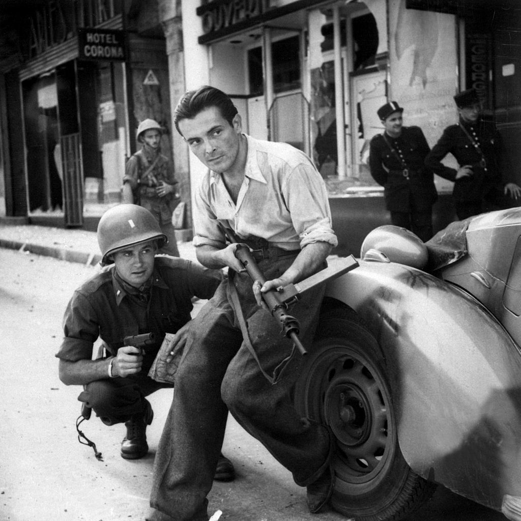 American Officer And French Partisan Crouch Behind An Auto During A Street Fight In City Ca HD SN 99 02714