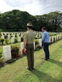 Andrew Wallace MP paying his respects at the grave of Flt Officer J.H. Borland from Caloundra in the Bomana War Cemetary in Papua New Guinea in the company of an ADF solder.png