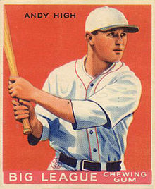 A baseball card image of a man in a white baseball uniform with red trim and white baseball cap with a black brim holding a baseball bat over his right shoulder