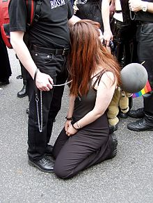 bdsm couple with the top standing and the bottom in handcuffs at