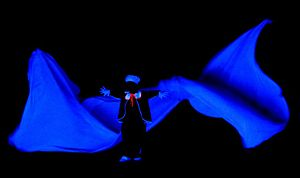 Black light theatre - Only parts of this performer's body can be seen because of the special costume.