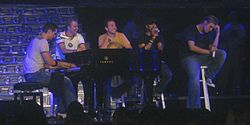 Backstreet Boys sitting on stools with microphones and singing, with one of them playing the piano.