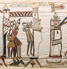 White embroidery showing several people on the left pointing to Halley, top right, over a tower