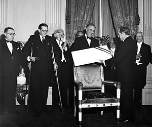 Cary T. Grayson - As chair of the national event, Grayson presents FDR with a $1 million check constituting the proceeds of the first President's Birthday Ball to benefit the fight against polio (May 1934)