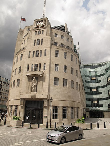 The British Broadcasting Corporation's landmark and iconic London headquarters, Broadcasting House, opened in 1932. At right is the 2005 eastern extension, the John Peel wing. Broadcasting House by Stephen Craven.jpg