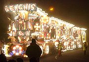 Night time photograph of lorry and trailer illuminated with thousands of light bulbs to make pictures. In the foreground and to the side are pedestrians.
