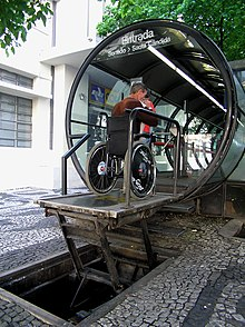 A special lift raises a wheelchair and its occupant to the platform of a bus stop