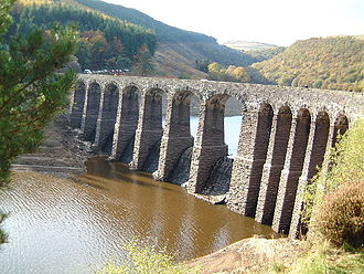 Elan Valley Reservoirs - Garreg-ddu dam seen at low water, summer 2003. Its job is to maintain a constant level in the reservoir during drought conditions so water can still enter the Elan Valley aqueduct.