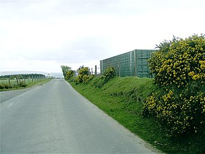 English: Container in field by military road A...