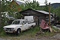 Datsun Pickup in Front of Log Cabin (16698201388).jpg