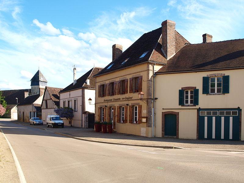 Dracy-sur-Ouanne (Yonne, France). Vue de la D 950, venant de Charny en direction du sud et de Toucy (la route continue vers l'est après le village). Le château est immédiatement à gauche de la photo, ses murs sont en bord de route.