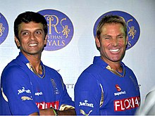 A dark coloured man in the left and a white coloured man in the right, both wearing blue shirts.
