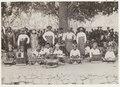 Een gamelanorkestje met daarachter een aantal kaja-spelers op Lombok, KITLV 29329.tiff