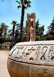 Hieroglyphs in Memphis with a statue of Ramses II in the background