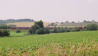 In summer 2007 a Regionalexpress crosses the formerInner German Border which ran along the stream in the foreground.