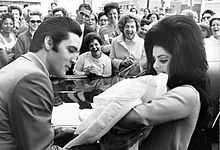 Photo of Elvis Presley kissing his new bride Priscilla