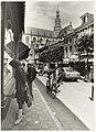 Etalages kijken in de Warmoesstraat. Op de achtergrond de Grote Kerk. NL-HlmNHA 54015496.JPG