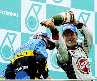 2006 Malaysian Grand Prix - Jenson Button pouring champagne on Giancarlo Fisichella during the podium ceremony after the race.