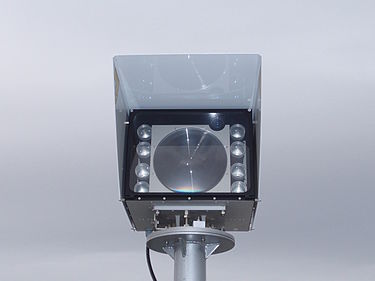 An 8-beam free space optics laser link, rated for 1 Gbit/s at a distance of approximately 2 km. The receptor is the large disc in the middle, the transmitters the smaller ones. To the top and right corner a monocular for assisting the alignment of the two heads. FSO-gigabit-laser-link-0a.jpg