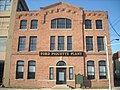 alt=A large brick building with a sign that says Ford Piquette Plant