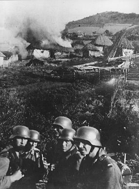 German soldiers set fire to a Serbian village near Mitrovica, circa 1941. Germans in Kosovska Mitrovica.jpg