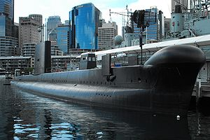 A submarine tied up alongside a wharf on a calm day. Numerous skyscrapers are in the background