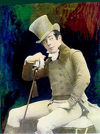 A young man dressed all in white with a matching top hat and cane sits, head cocked, looking to his left