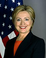 Hillary Clinton wearing a dark jacket over an orange blouse. The United States flag is in the background.